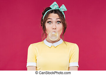 Amazed cute pinup girl blowing a bubble gum balloon - Amazed...