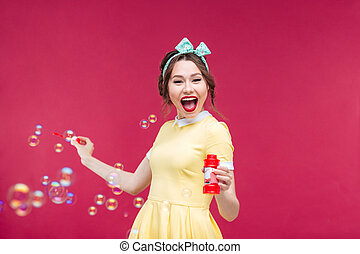 Cheerful pretty young woman having fun with soap bubbles...
