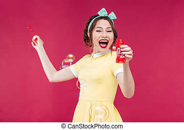 Happy excited pinup girl blowing soap bubbles and laughing -...