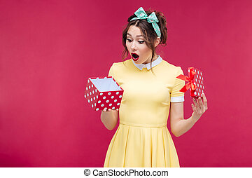 Wondered cute young woman opening gift box over pink...