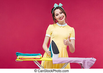 Happy lovely pinup girl ironing clothes and showing thumbs...