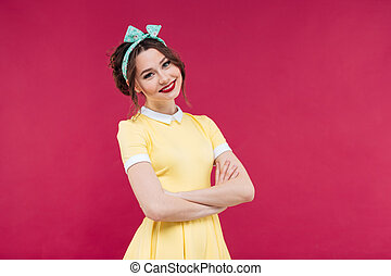 Smiling young woman in yellow dress standing with arms crossed