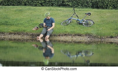 Happy mature man using smartphone against lake Man with...