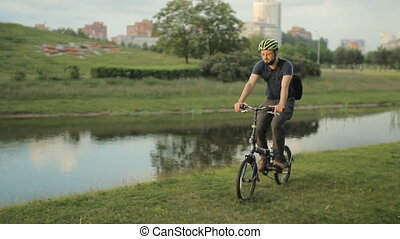 Man on bicycle riding to the park with laptop