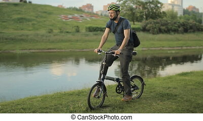 Man on folding bicycle with tablet