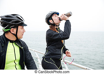 Two cyclists resting near sea Woman drinking water and man...