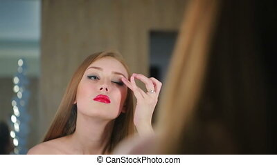 girl puts make-up before a mirror. She is going on a date -...