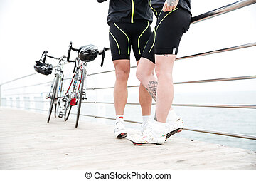 Couple in bike shorts with bicycles standing on pier -...