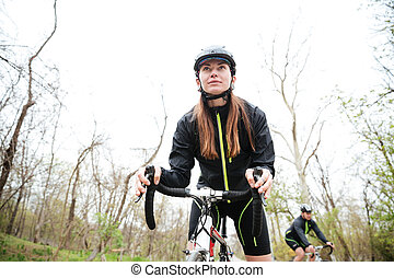 Woman riding bike in park - Concentrated young woman riding...
