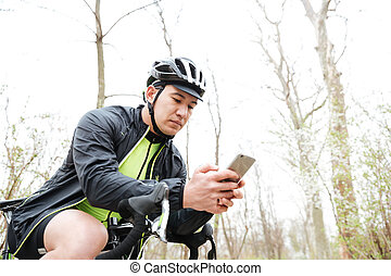 Man in cycling helmet with bicycle using smartphone in park...