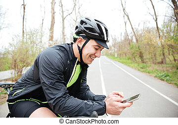 Cheerful young man with bicycle using mobile phone - Serious...