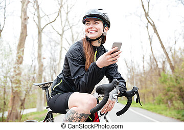 Happy woman in cycling helmet on bicycle using smartphone -...