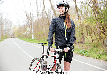 Smiling woman with bicycle walking on the road