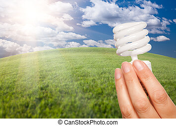 Female Hand with Energy Saving Light Bulb Over Field -...