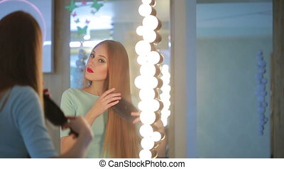 combed woman in the mirror. He is going on a date. long hair