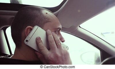 businessman talking on his cell phone while drives the car...