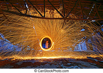 Burning Steel Wool spinning. Showers of glowing sparks from...