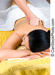Woman receiving deep back massage at spa - Young female...