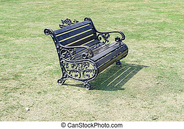 Single park bench on the green grass in the lawn.