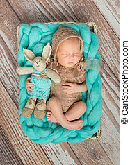 adorable newborn baby with bunny-toy in cot - adorable...