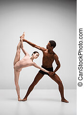 Couple of ballet dancers posing over gray background -...