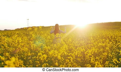 beautiful girl walks on field of flowers at sunset