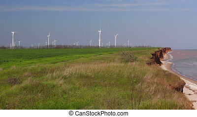 Sea coast and farm of wind mill turbines. Green energy...