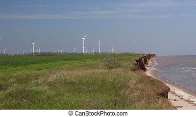 Sea coast and farm of wind mill turbines. Green energy...