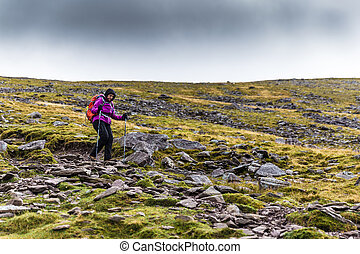 Femal hiker hiking downhill from a mountain crossing a rocky...
