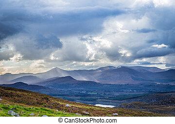 Sun rays piercing through the clouds touching the Irish...