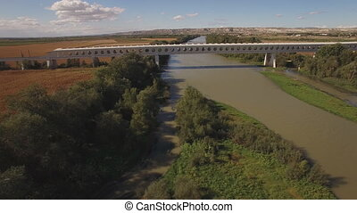 Modern train bridge over ebro river - Side view of train...