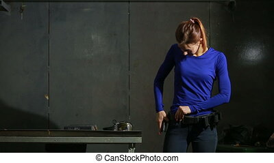 young woman with the gun on an indoor shooting range...