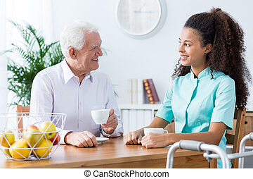 You're like daughter to me - Carer and senior man drinking...