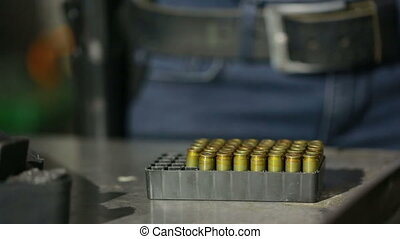 young woman with the gun. indoor shooting range. charges cartridges in the gun