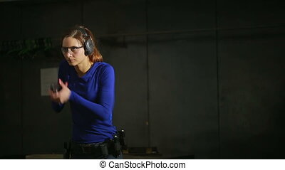 Beautiful young woman with the gun on an indoor shooting range. shoots a gun