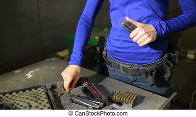 young woman with the gun. indoor shooting range. charges...