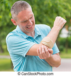 Man wearing elbow brace to reduce pain