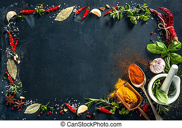 Herbs and spices over black stone background. Top view with...