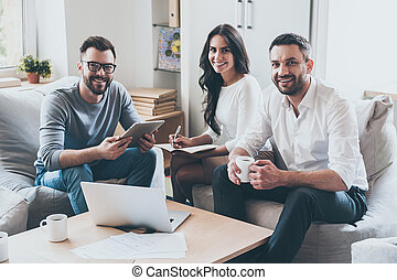 Successful team. Three confident business people in smart casual wear looking at camera and smiling while sitting together at the desk in office