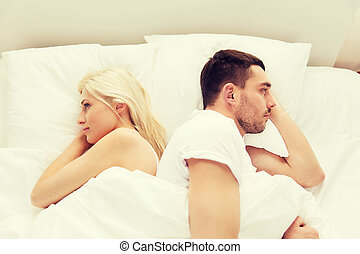 unhappy couple lying in bed at home - people, relationship...