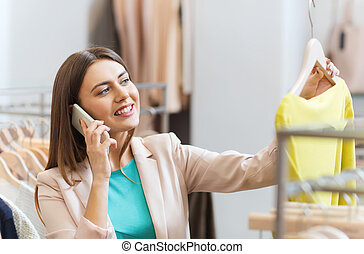 woman calling on smartphone at clothing store - sale,...