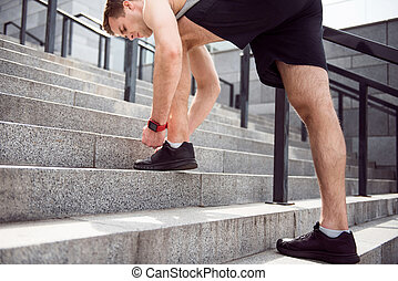 Man tying shoelaces on stairs - Ready to run Young...
