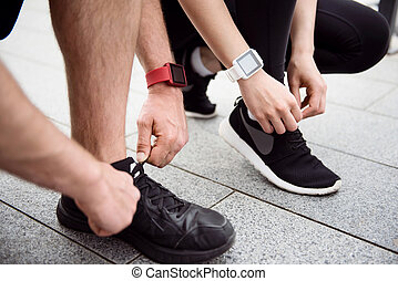 Man and woman tying their shoelaces - Necessary steps...
