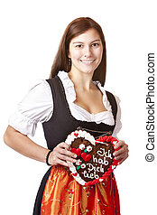 woman in love wearing Dirndl cloth holds gingerbread heart...
