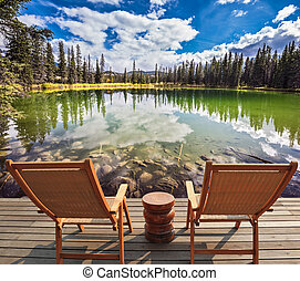 Two wooden deckchairs before  lake