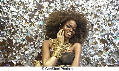 Creative surreal portrait of sexy african american female model with gold glossy makeup Face art. Silver glossy confetti background