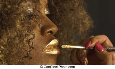 Close-up of magic golden african american model with bright glitter makeup and golden glossy hairstyle preparing for shooting at the stylist in studio backstage