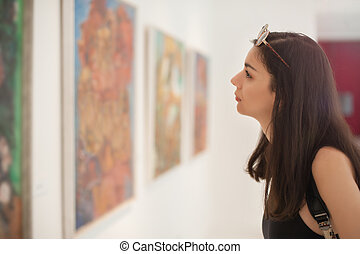 Art gallery - Young woman looking at modern painting in art...