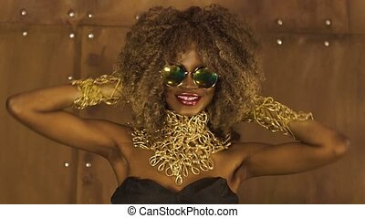 Magic surreal golden african american female model in massive sunglasses with bright glitter makeup,