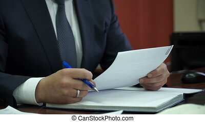businessman sitting in an office signing a contract -...